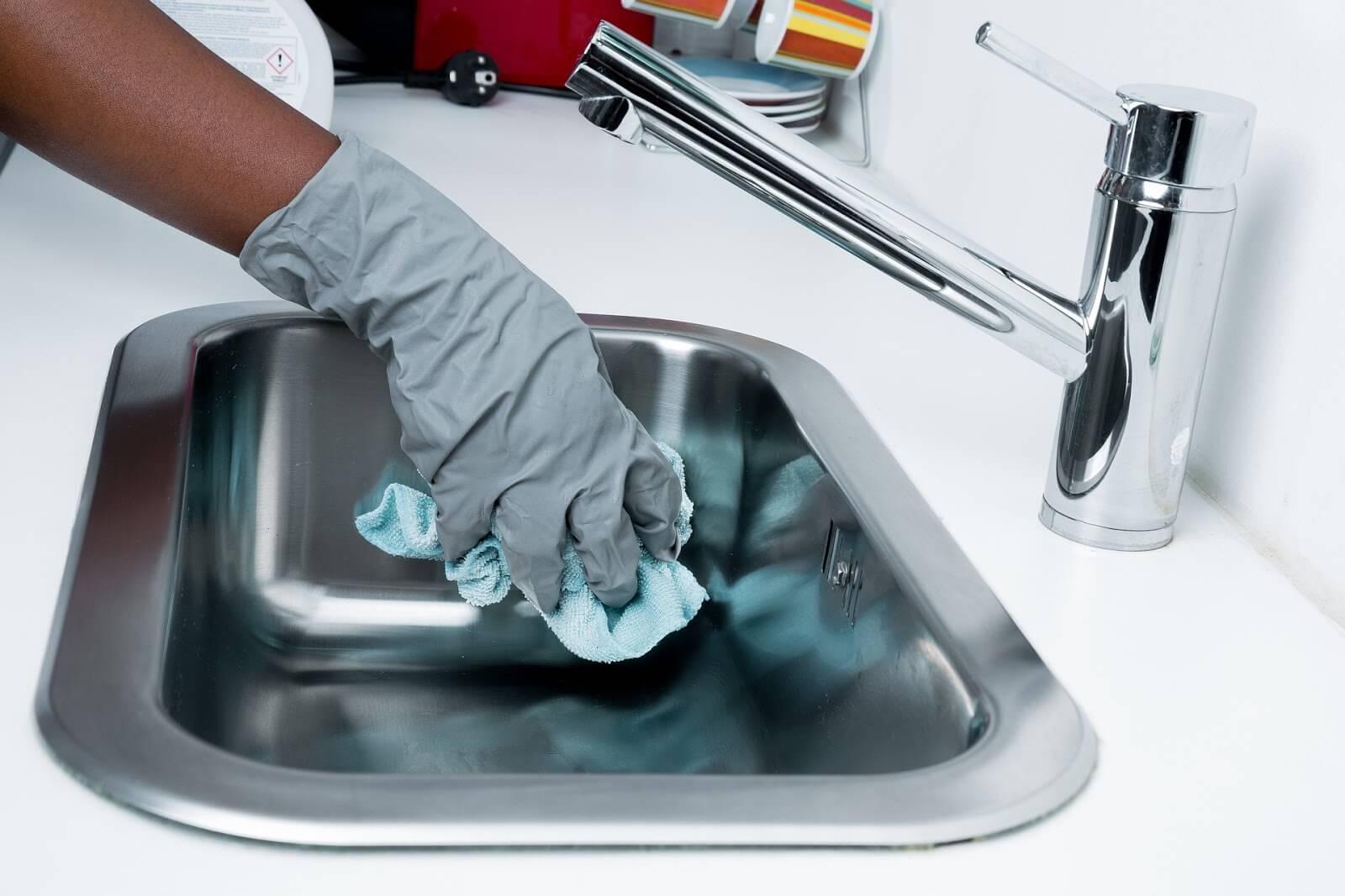 Trabajos de limpieza de la casa: Una mano que lleva un guante de limpieza limpia frega un fregadero