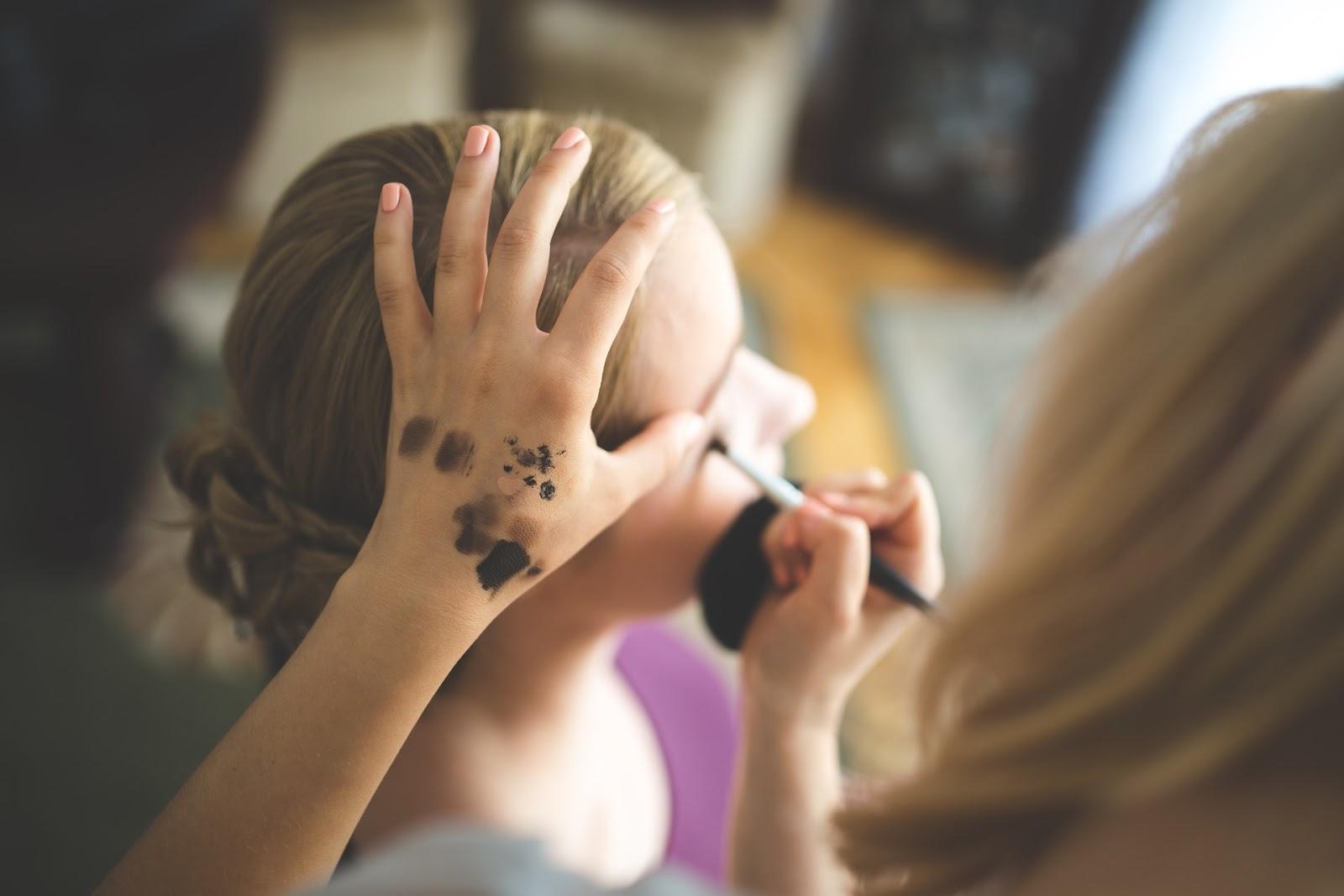 A makeup artist works on a client