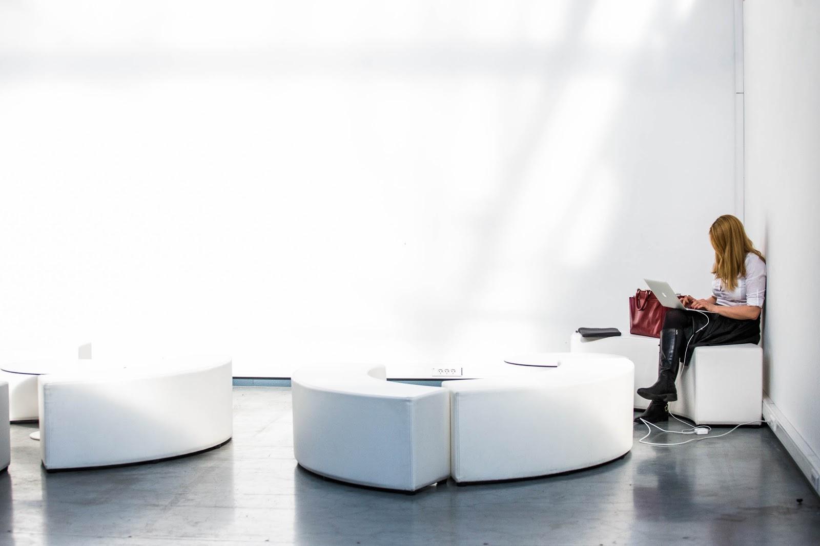 Estudiante que trabaja en la computadora portátil en una habitación blanca