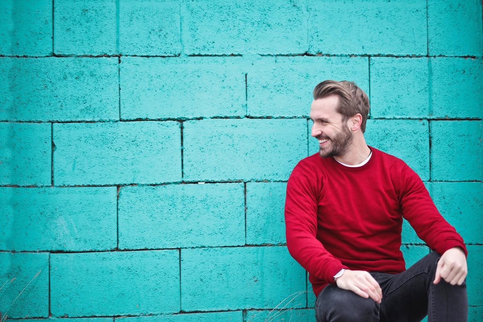 hombre sentado contra la pared riendo
