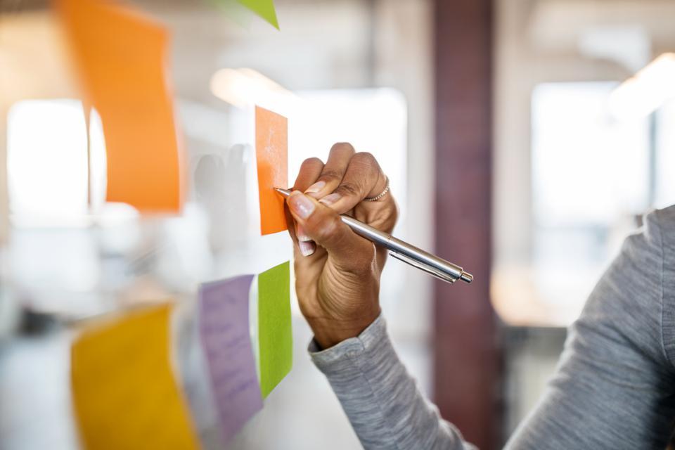 Mujer escribiendo nuevas ideas en una nota adhesiva para ayudar con la planificación y la lluvia de ideas de inicio de tecnología
