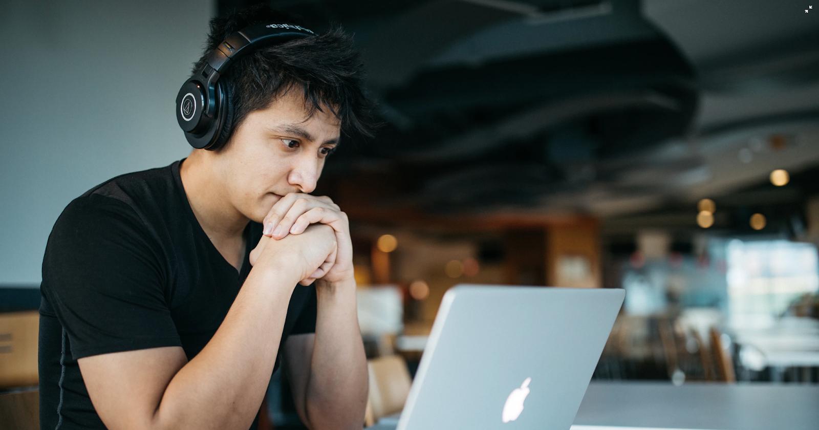 persona con auriculares mirando la computadora