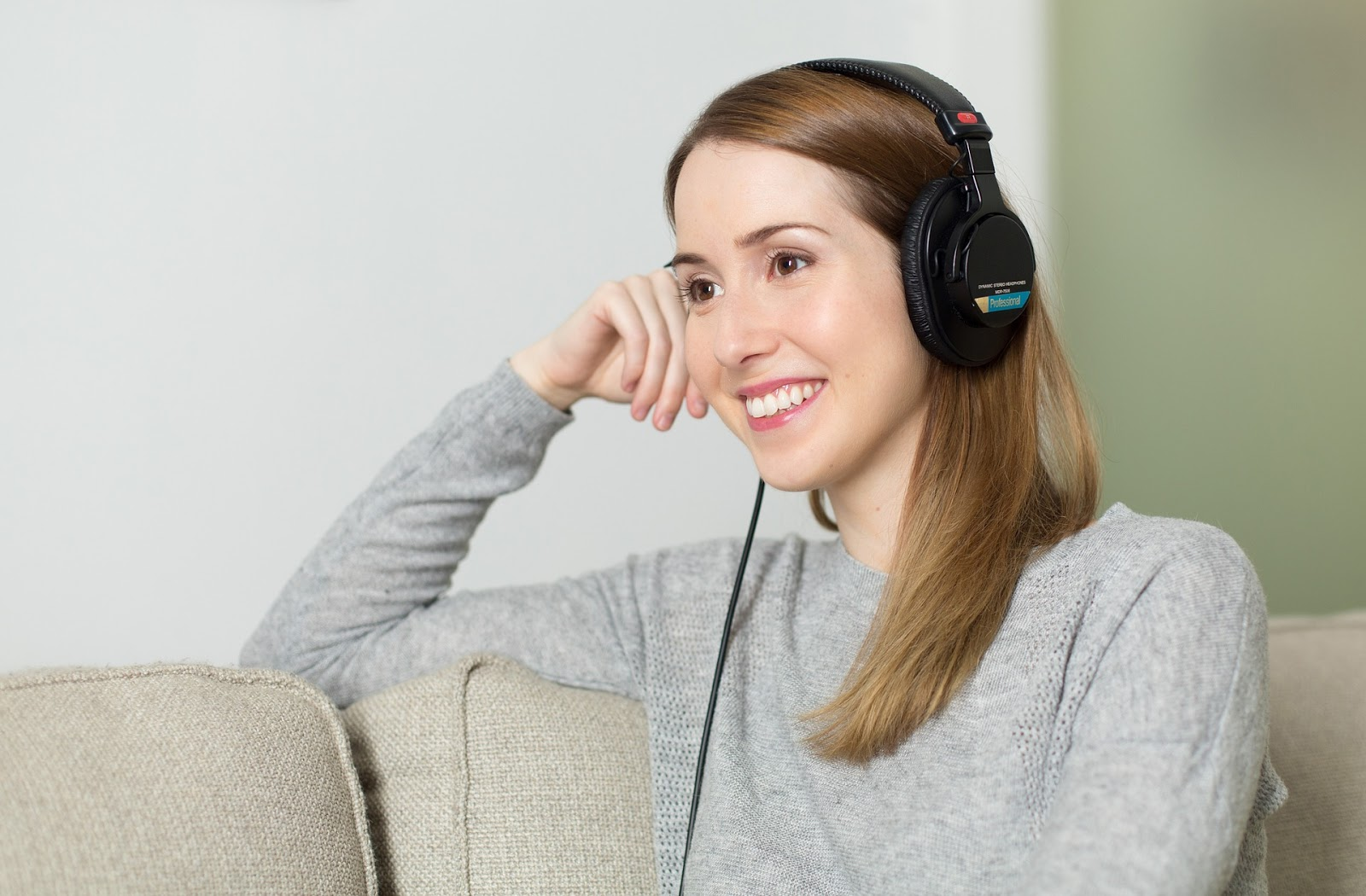 LanguageLine: una mujer se sienta en su sofá y escucha los auriculares