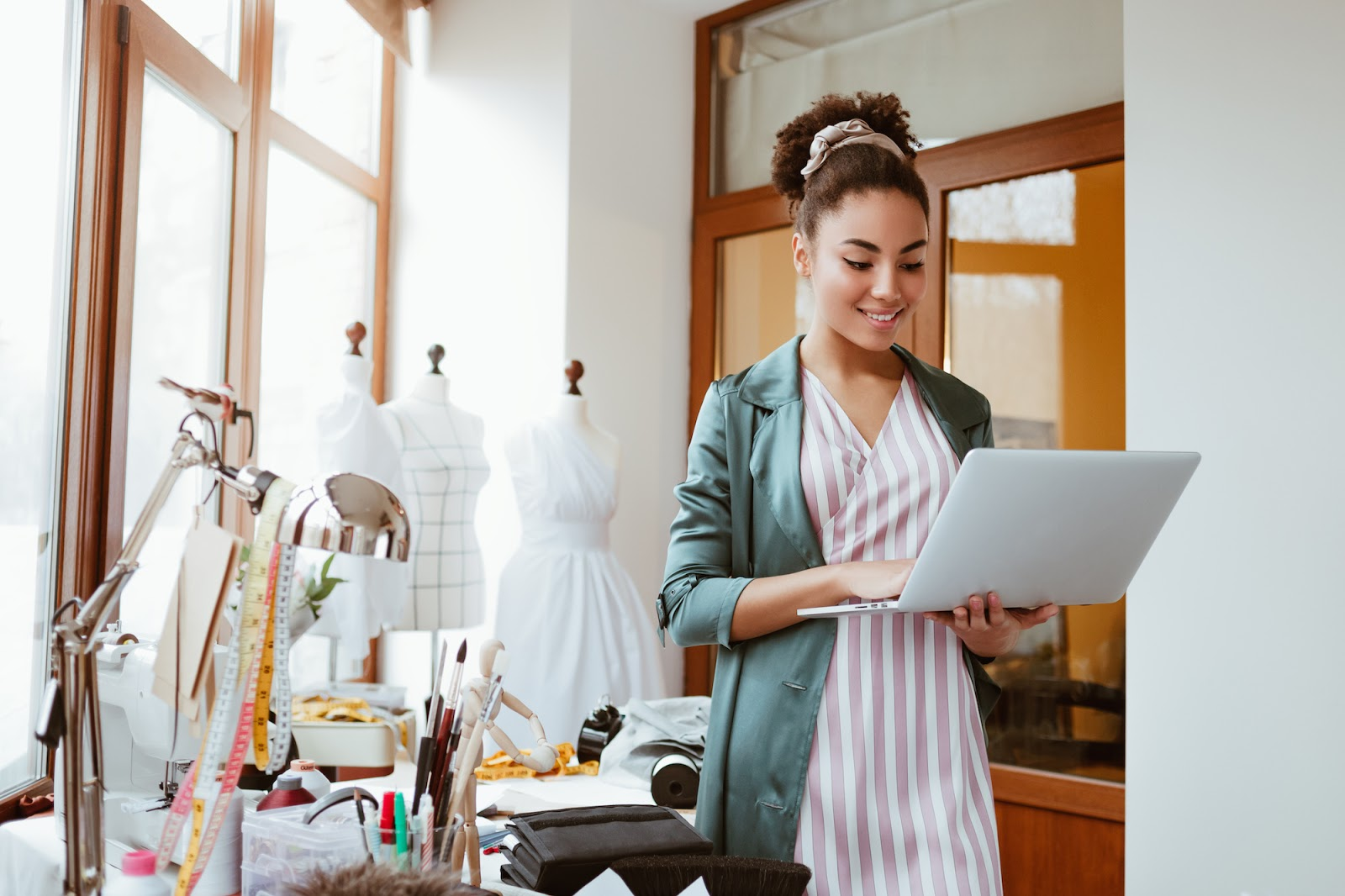 Cómo convertirse en estilista personal en línea: mujer sosteniendo su computadora portátil sonriendo