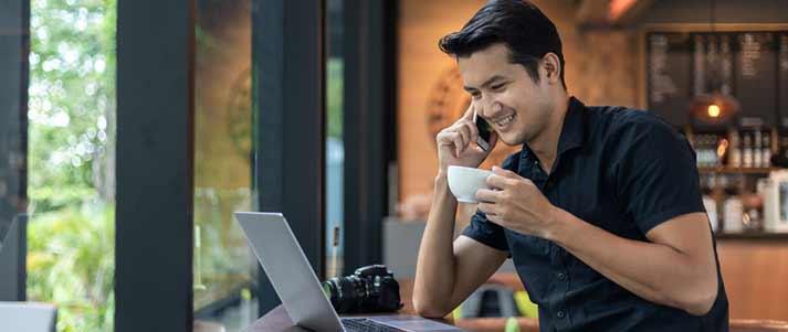 hombre trabajando en el teléfono en la cafetería