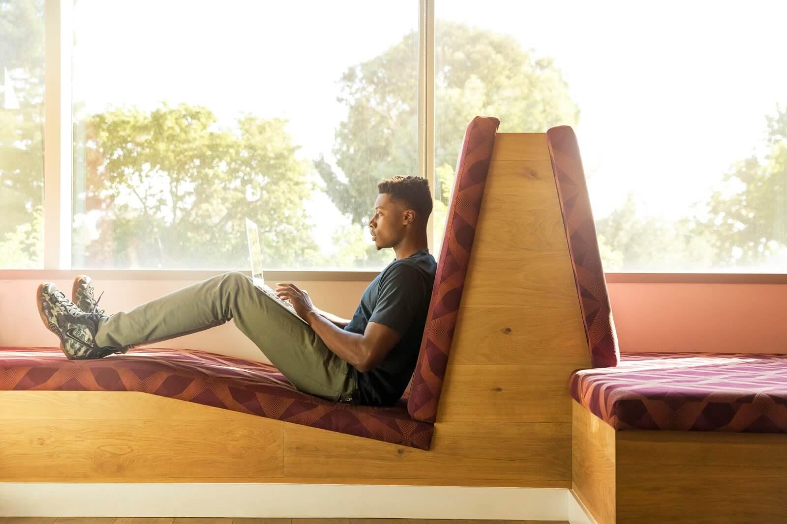 Buscando trabajos en línea para adolescentes en una silla junto a una ventana